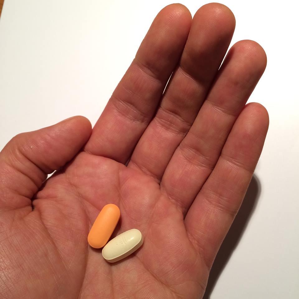 Eine Hand mit zwei ovalen Tabletten darin