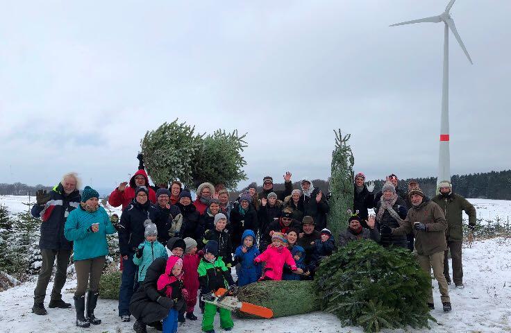 Menschen stehen im Schnee mit Tannenbäumen vor einer Windkraftanlage